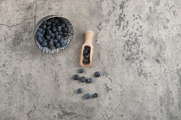 Keramikschale mit leckeren frischen blaubeeren auf marmoroberfläche