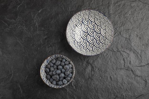 Keramikschale mit leckeren frischen blaubeeren auf schwarzer oberfläche