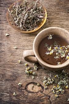 Keramiktasse mit tee aus getrockneter kamille und heilkräutern gebraut