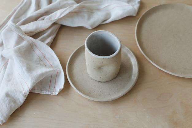 Keramiktasse und teller auf einem holztisch draufsicht minimalistisches set aus handgefertigtem keramikgeschirr und ...