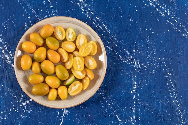Keramikteller mit geschnittenen frischen kumquatfrüchten auf marmoroberfläche