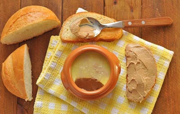 Keramiktopf und löffel mit pastete und toastbrot auf einer serviette. holzhintergrund