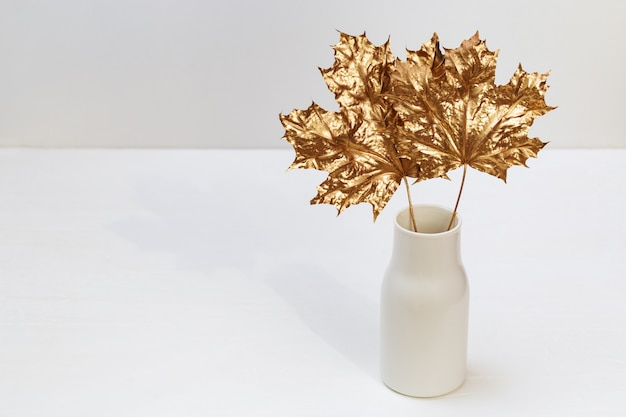 Keramikvase mit goldenen blättern des marplebaums.
