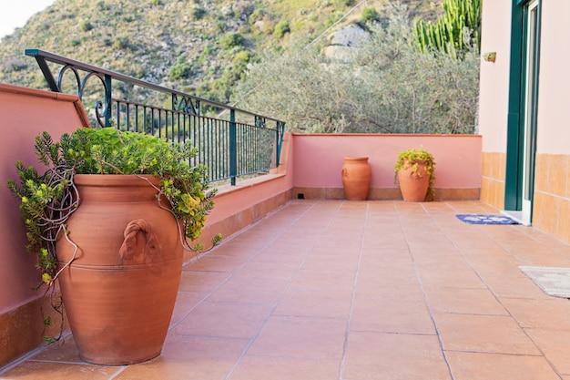 Keramikvasen für olivenöl schmücken die balkone in sizilien.
