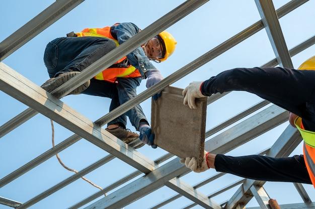 Keramische dachziegel installation durch dachdecker, konzept des im bau befindlichen wohngebäudes.