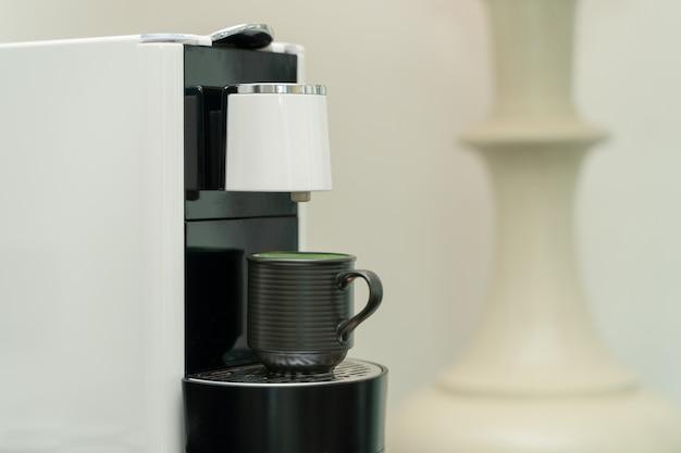 Keramische tasse kaffee auf der kaffeemaschine. kaffeekapselmaschinenhersteller.