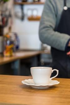 Keramische tasse und untertasse des kaffees auf kaffeebarzähler