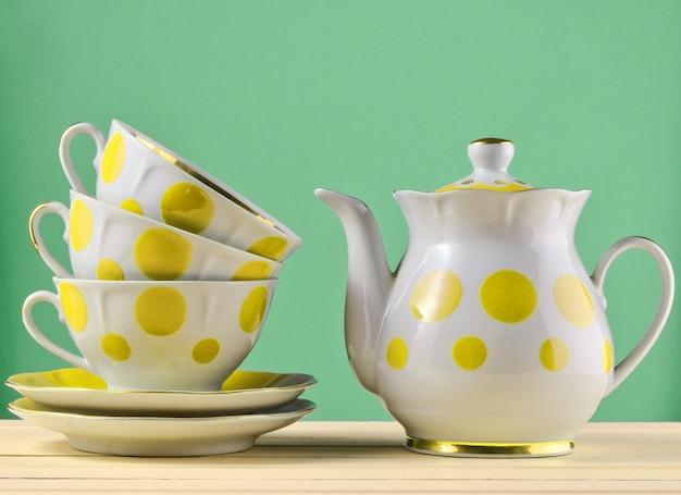 Keramische teekanne, ein stapel tassen in tupfen auf einem holztisch