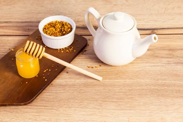Keramische teekanne mit dem blütenstaub und hölzernem hintergrund des honigs