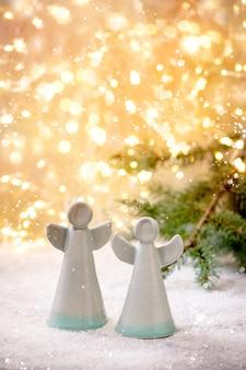 Keramische weihnachtsengel. satz von zwei handgefertigten weihnachtsdekorationsengeln auf schnee mit bokeh-feiertagslichtern und tannenzweigen.
