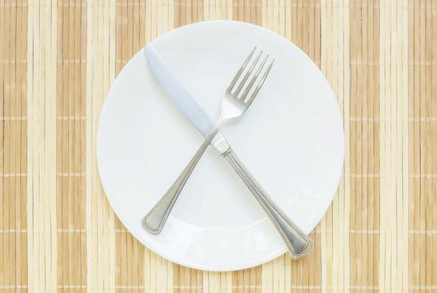 Keramischer teller der nahaufnahme mit rostfreier gabel und messer im unfertigen essenmittel