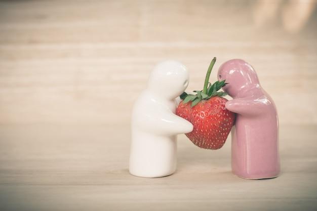 Keramisches spielzeug, das eine erdbeere zum verbinden für ihre liebe gibt