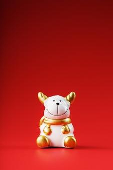 Keramisches weihnachtskuhstierspielzeug auf einem roten hintergrund
