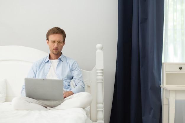 Kerl arbeitet mit laptop in seinem bett zu hause. ruhiger friedlicher mann mittleren alters, der pyjamas und dünne klare gläser trägt, die in seinem bett unter der decke sitzen und mit computer arbeiten