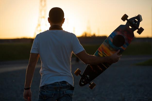 Kerl betrachtet den sonnenuntergang, der ein longboard in seiner hand hält