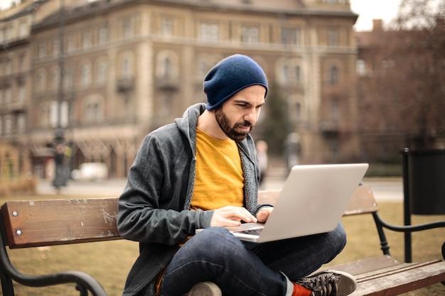 Kerl, der an einem laptop auf der straße arbeitet