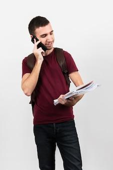 Kerl, der an seinem telefon spricht und anmerkungen hält