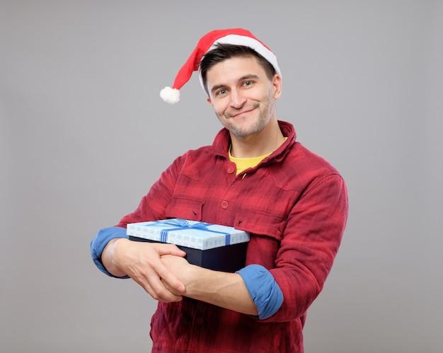 Kerl, der ein weihnachtsgeschenk hält