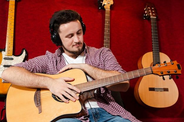 Kerl, der eine akustikgitarre hält und das instrument betrachtet