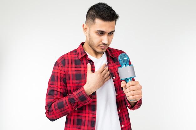 Kerl, der eine rede vorbereitet, die ein mikrofon in seiner hand auf einem weißen isolierten hintergrund mit kopienraum hält.