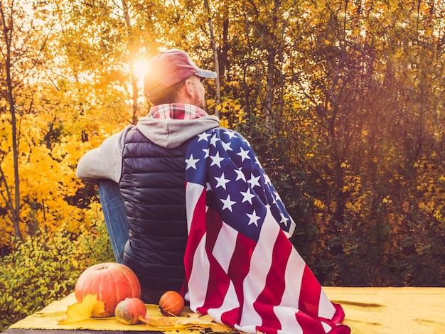 Kerl, der eine us-flagge hält. nationalfeiertag