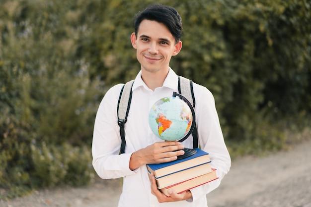Kerl, der einen stapel bücher mit einem globus hält