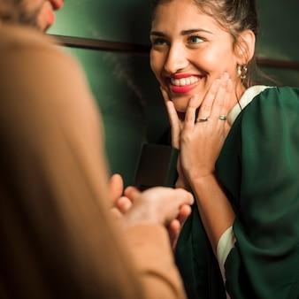 Kerl, der geschenk im kasten attraktiver glücklicher dame darstellt