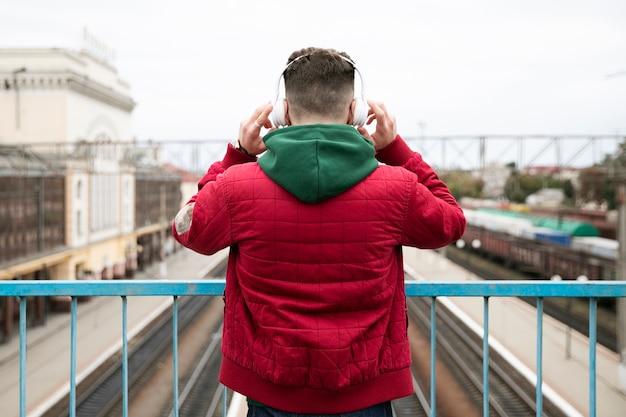 Kerl der hinteren ansicht mit kopfhörern auf einer brücke