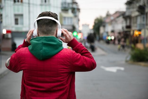 Kerl der hinteren ansicht mit kopfhörern und warmer kleidung
