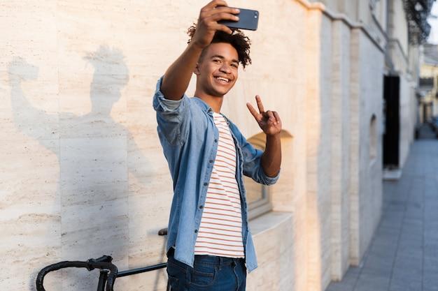 Kerl, der mit dem fahrrad draußen auf der straße geht, macht ein selfie per handy