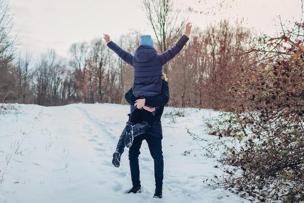 Kerl, der seine freundin in den händen im winterwald hält und anhebt. frau, die arme anhebt. leute, die spaß draußen haben