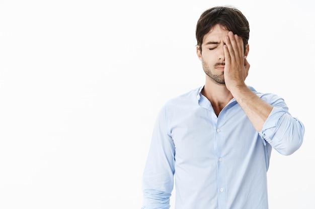 Kerl, der sich traurig fühlt, verpasst die gelegenheit, sein leben lang schuldig und verärgert zu sein, indem er eine facepalm-geste mit der hand auf dem gesicht macht, die mit geschlossenen augen steht, sich ausgelaugt und unwohl fühlt, nachdem er gefeuert wurde