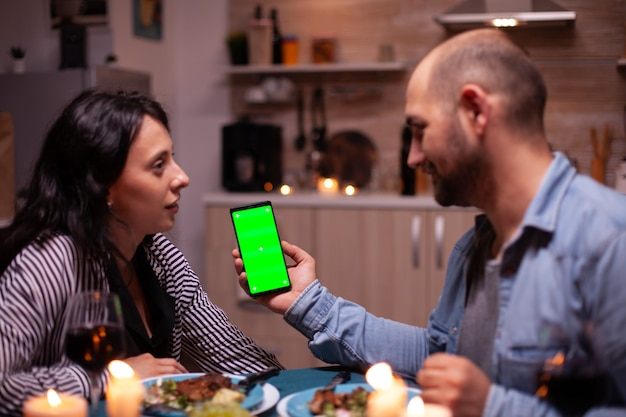Kerl, der telefon mit grünem bildschirm hält, während er ein romantisches abendessen mit seiner frau hat. viel spaß beim betrachten der greenscreen-vorlage chroma-key isolierte smartphone-anzeige mit technologie-internet.