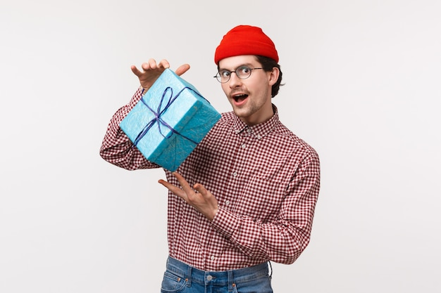 Kerl, der versucht, intrigen als vorbereitetes geschenk für freundin zu machen, verpackte schachtel mit geschenk zu schütteln, sich zu fragen, was drin ist, mysteriöse und gerissene kamera zu sehen, rotes beanie-kariertes hemd zu tragen,