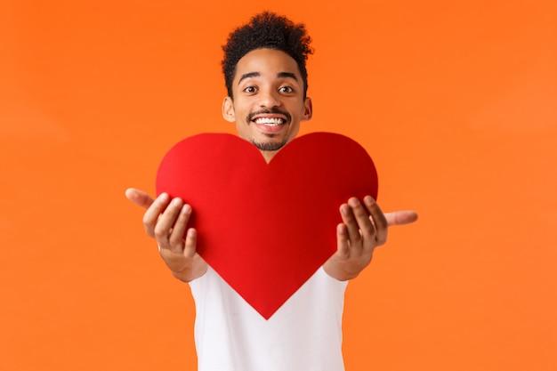 Kerl gibt seine liebe dich. hübscher reizender afroamerikanischer mann, der hände streckt und präsentiert
