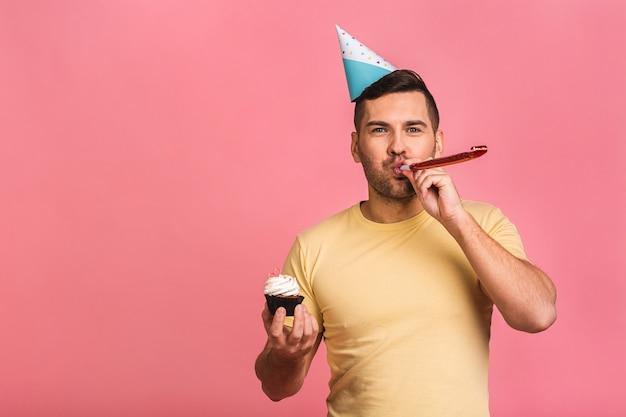Kerl halten kleinen kuchen und feiern geburtstag. einsam auf party. allein feiern.