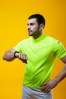 Kerl im gelben t-shirt, das auf kamera aufwirft
