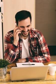 Kerl im hemd unter verwendung des telefons und des trinkenden kaffees