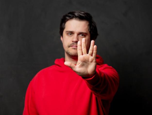 Kerl im roten sweatshirt zeigen vulkanischen gruß an dunkler wand