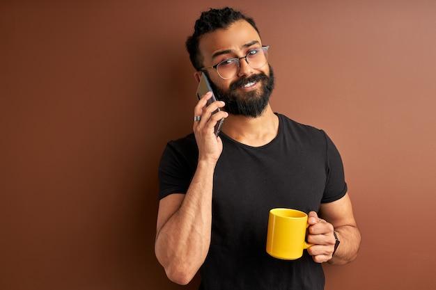 Kerl in brillen sprechen am telefon, mischrasse indischer arabischer mann trinken tee oder kaffee am morgen und haben gespräch mit smartphone