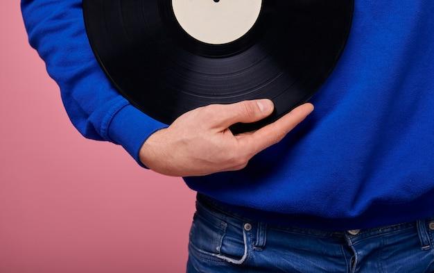 Kerl in der blauen strickjacken- und denimhose auf hintergrund hält schwarze vinylaufzeichnung in seiner hand.
