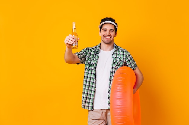 Kerl in der kappe und im weißen t-shirt, das flasche bier und orange aufblasbaren kreis auf isoliertem raum hält.