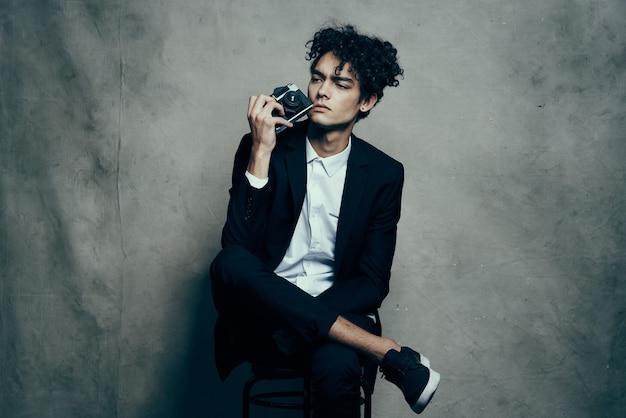 Kerl in einem klassischen anzug drinnen mit einer kamera in der hand und turnschuhen brunet hobby