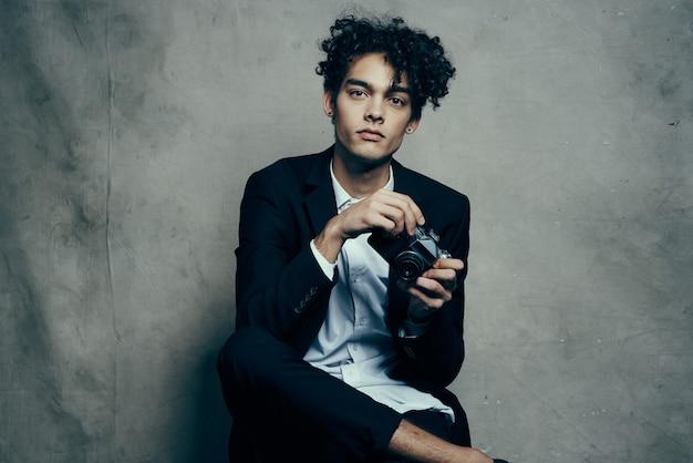 Kerl in einem klassischen anzug mit einer kamera auf einem stoffhintergrundhobby