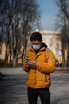 Kerl in einem park mit einer baumwollmaske als zusätzlichen schutz