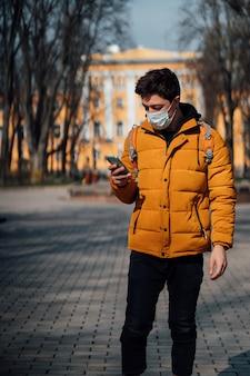 Kerl in einem park mit einer maske als zusätzlichen schutz