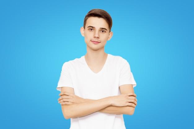 Kerl in einem weißen t-shirt faltete die hände, die auf einem blauen hintergrund, freundlicher mann lokalisiert wurden