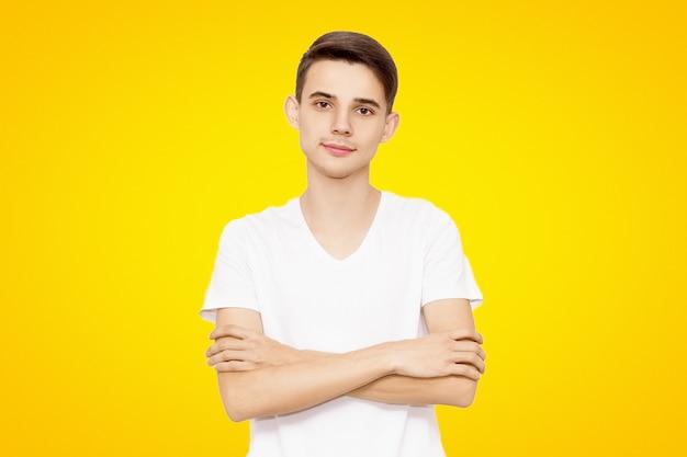Kerl in einem weißen t-shirt faltete die hände, die auf einem gelben hintergrund, freundlicher mann lokalisiert wurden