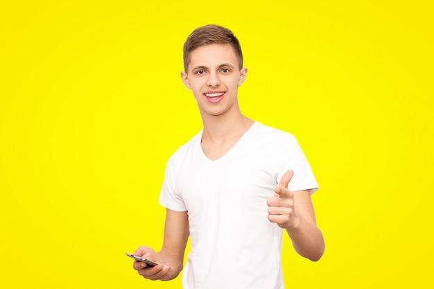 Kerl in einem weißen t-shirt hält ein telefon und zeigt der kamera einen finger