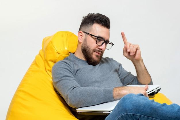 Kerl in gedanken beim sitzen auf gelbem hocker stuhl